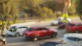 De autoverkeerslichten van de Defocusedstad Vaag beeld bij zonsondergangdag De auto's gaan en bevinden zich op de weg Het concent stock footage