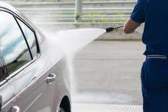De autowasserettearbeider wast de modder met onder water Stock Fotografie