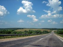 De autoweg in de barsten gaat ver in de afstand op een heldere Zonnige dag stock afbeelding