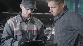 De autowerktuigkundige en de autoeigenaar bevinden zich bespreken reparatie van auto, toont de arbeider berekeningen stock videobeelden