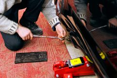 De autowerktuigkundige installeert een mechanische en hydraulische hefboom voor autoreparatie stock foto's
