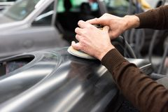 De autowerktuigkundige maalt een autodeel in ambacht in een benzinestation - Serie-de workshop van de autoreparatie stock foto