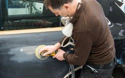 De autowerktuigkundige maalt een autodeel in ambacht in een benzinestation - Serie-de workshop van de autoreparatie stock foto's