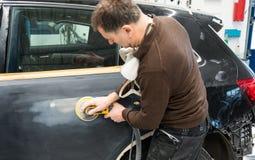 De autowerktuigkundige maalt een autodeel in ambacht in een benzinestation - Serie-de workshop van de autoreparatie stock fotografie
