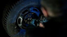 De autowerktuigkundige in vuile autoreparatiewerkplaats herstelt de auto stock footage