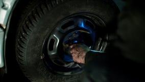 De autowerktuigkundige in vuile autoreparatiewerkplaats herstelt de auto stock video