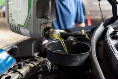 De autowerktuigkundige vult een verse olie van de smeermiddelmotor royalty-vrije stock fotografie