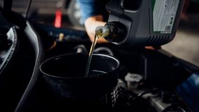 De autowerktuigkundige vult een verse olie van de smeermiddelmotor stock foto