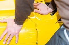 De autowerktuigkundigen richten correct de bonnet wanneer het assembleren - Serie-Reparatieworkshop royalty-vrije stock afbeeldingen