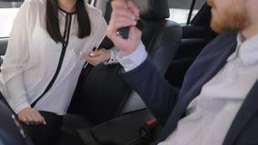 De autozaken, de arbeidersmeisje van de autowinkel adviseren de cliënt na sleutels aan automobiele eigenaar geeft en handen binne stock videobeelden