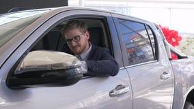 De autozaken, de nieuwe auto van de kerelsaus van de consument en tonen sleutels die in salon zitten en door venster op verkoopce stock videobeelden