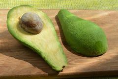 De avocado met been zonder huid wordt gesneden op een eiken raad stock afbeeldingen