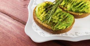 De avocado op roggebrood voor gezond ontbijt stemde selectieve nadruk Stock Afbeeldingen