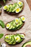 De avocadosandwich op donker roggebrood maakte met verse gesneden avocado's met spinazie, guacamole, arugula en kwartelseieren Stock Afbeelding