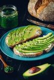 De avocadosandwich op donker roggebrood maakte met verse gesneden hierboven avocado's van stock afbeelding