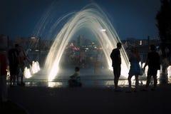 De avond bij de fontein op de waterkant Stock Foto