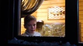 De avond van de winter In een warme en heldere ruimte dichtbij het venster bevindt zich een jonge mens In openlucht het ontspruit stock videobeelden