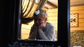 De avond van de winter In een warme en heldere ruimte dichtbij het venster bevindt zich een jonge mens het werpen van een sneeuwb stock video