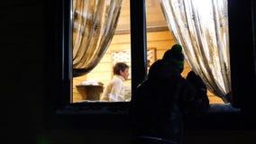 De avond van de winter In een warme en heldere ruimte dichtbij het venster is een jonge mens en slagen op het venster In openluch stock videobeelden