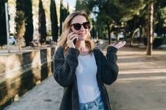 De avond van de zomer Een jonge aantrekkelijke vrouw in zonnebril bevindt zich in het park en spreekt gelukkig op haar celtelefoo stock afbeelding