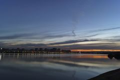 De avondzonsondergang over de stad op de banken van de rivier royalty-vrije stock fotografie