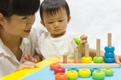 De Aziatische aanbiddelijke baby één jaar speelt de piramide van het kleurenraadsel voor stock fotografie