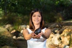 De Aziatische avocado van de vrouwenholding Royalty-vrije Stock Foto's