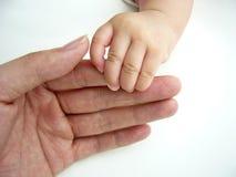 De Aziatische baby dient volwassen hand in Stock Foto