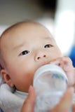 De Aziatische baby is het drinken melk Stock Foto