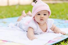De Aziatische baby ligt naar voren gebogen op grond bij park Stock Foto