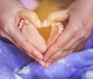 De Aziatische babyvoeten in de moeder overhandigt gevormd hart Stock Foto's
