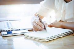 De Aziatische Bedrijfsvrouw schrijft de nota over leeg notitieboekje Stock Afbeelding