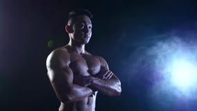 De Aziatische bodybuilder toont zijn lichaam, sterkte en duurzaamheid aan Zwarte rookachtergrond Langzame Motie stock videobeelden