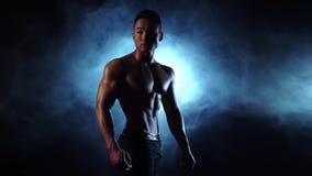 De Aziatische bodybuildermens toont zijn lichaam, sterkte en duurzaamheid aan Zwarte rookachtergrond Langzame Motie stock video