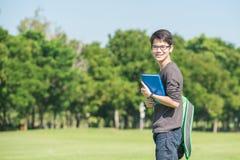 De Aziatische boeken van de studentenholding en het glimlachen terwijl status in park a Royalty-vrije Stock Foto