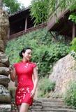De Aziatische Chinese chi-pao cheongsam vrouw met klassieke geborduurde ventilator geniet van het ontspannen oostelijke kenmerk v royalty-vrije stock afbeeldingen