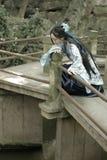 De Aziatische Chinese vrouw in traditionele Blauwe en witte Hanfu-kleding, spel in een beroemde tuin beklimt op de gebogen brug Royalty-vrije Stock Fotografie