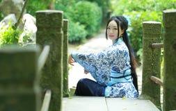 De Aziatische Chinese vrouw in traditionele Blauwe en witte Hanfu-kleding, spel in een beroemde tuin, zit op de brug stock foto