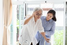 De Aziatische dochter of de zorgmedewerker die steun hogere vrouw of moeder helpen, delen de symptomen van duizeligheid mee; duiz royalty-vrije stock foto's