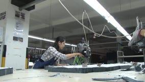 De Aziatische Fabriek van de Kledingstukindustrie: Arbeiders bij een stoffen scherpe lijst met lintzaag stock footage