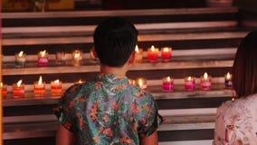 De Aziatische familie, de Moeder en de zoon nemen lichten een kaars bij de Boeddhistische tempel stock video