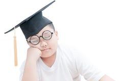 De Aziatische gediplomeerde slaap van het schooljonge geitje met geïsoleerde graduatie GLB Royalty-vrije Stock Afbeelding