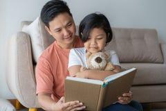 De Aziatische gelezen vader en de dochter boeken de vloer in het huis, Self-learning concept royalty-vrije stock foto's