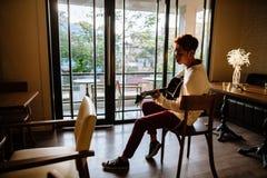De Aziatische gitaar van het de mensenspel van de gitaristkunstenaar in koffie Stock Foto