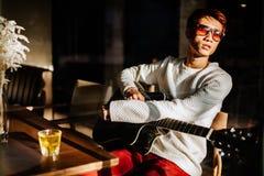 De Aziatische gitaar van het de mensenspel van gitaristartiist in koffie Royalty-vrije Stock Foto