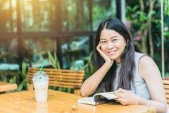 De Aziatische glimlach van de vrouwen Thaise tiener met boek in koffiewinkel royalty-vrije stock foto
