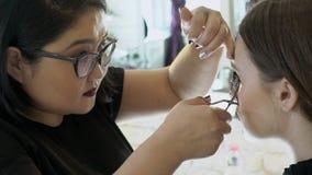 De Aziatische grimeur krult de wimpers van haar vrouwelijke cliënt met een speciaal hulpmiddel in salon stock video