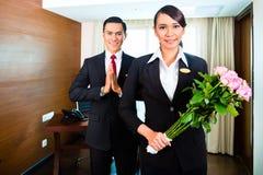 De Aziatische groet van het hotelpersoneel met bloemen Stock Afbeeldingen