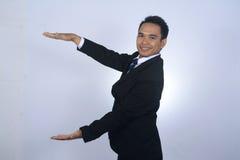 De Aziatische hand van de zakenmanholding met open palm die iets gebaar, concept tonen reclameproduct, lege mede Royalty-vrije Stock Foto's
