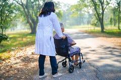 De Aziatische hogere of bejaarde oude patiënt van de damevrouw zorvuldig, hulp en steun op rolstoel in park in vakantie royalty-vrije stock foto's